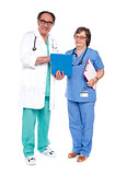 Doctor and nurse analyzing report together