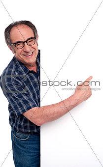 Causal matured man pointing finger at placard