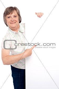 Causal senior lady pointing towards placard