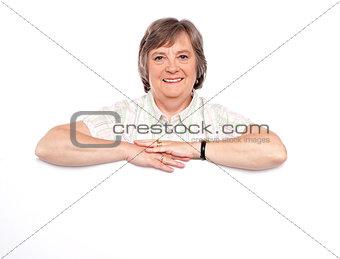 Aged woman standing behind blank billboard