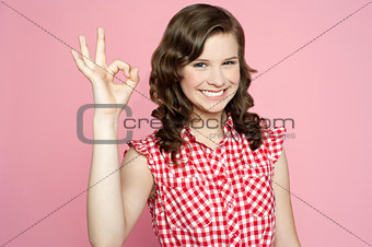 Attractive smiling teenager showing ok sign