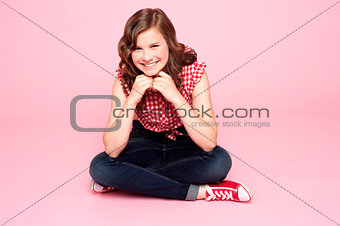 Caucasian girl sitting with hands on chin