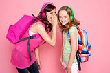 Trendy schoolgirls sharing a secret