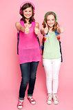 Happy teen girls showing thumbs up
