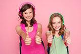 Two beautiful schoolgirls giving thumbs up