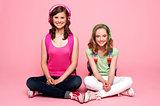 Two school friends sitting on studio floor