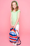 Young girl with schoolbag posing in studio