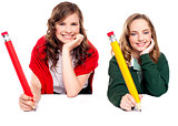 Beautiful schoolgirls posing with big pencil