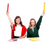 Students showing big pencil in raised arm