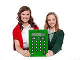 Girls showing big green calculator to camera