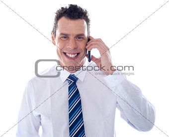 Smiling businessman attending phone call