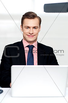 Attractive smiling man operating a laptop