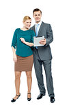 Businessman using tablet pc with secretary beside