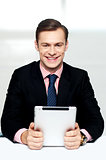 Cheerful male executive holding digital device