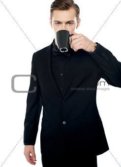 Smart young man drinking coffee in black cup