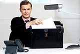 Male executive keeping documents safely