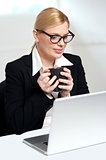 Female executive looking at laptop holding mug