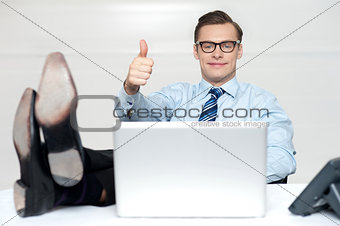 Thumbs up guy relaxing with legs on work desk