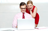 Shocked woman looking into laptop. Man working