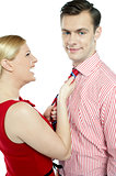 Glamorous woman pulling man by his tie