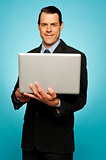 Attractive businessman holding laptop