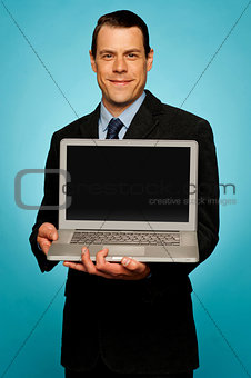 Corporate executive showing laptop to you