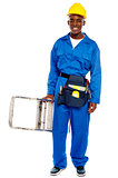 African repairman holding stepladder