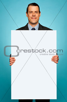 Corporate man holding big white blank billboard