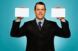 Businessman showing two blank white placards