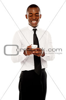 African male manager reading message on mobile