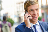 Attractive young businessman on the phone in urban background
