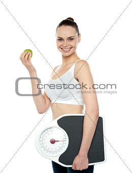 Attractive woman with apple and weight scale