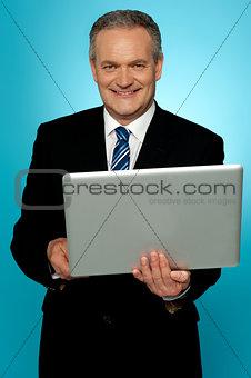 Smiling aged executive holding laptop