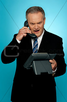 Angry aged corporate man yelling on phone