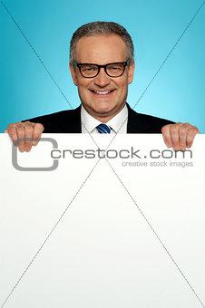 Corporate man standing behind big blank billboard