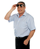 Casual man holding sunglasses over his head