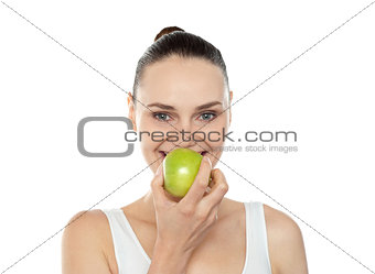 Attractive girl eating fresh juicy green apple