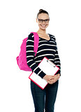 Smiling college girl carrying school bag and clipboard