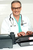 Smiling physician in eye wear typing on keyboard