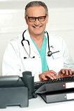 Smiling physician in eye wear typing on keyboard