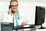 Aged doctor attending call in front of lcd screen