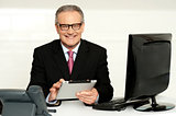 Aged businessman in glasses using tablet