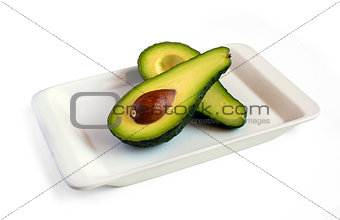 fresh avocado cut in half on square plate