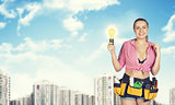 Woman in tool belt holding light bulb. Blurred buildings as backdrop