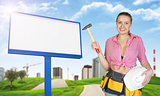 Woman holding hammer and helmet. Green hills, road, empty billboard, buildings as backdrop