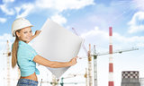 Woman holds white paper. Looking at camera, smiling. Cranes and heat power stations on background