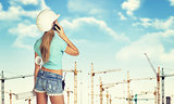 Girl in helmet holding paper roll and talking on phone. Tower cranes as backdrop