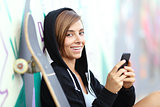 Teenager skater girl using a smart phone looking at camera