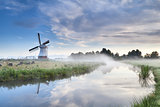 windmill and river in foggy morning