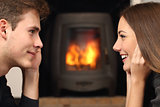 Couple looking each other in front a fireplace